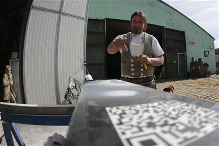 German mason Timothy Vincent looks at a QR code engraved onto a gravestone in the Austrian village of Boeheimkirchen about 65km (40 miles) west of Vienna September 21, 2012. REUTERS/Leonhard Foeger