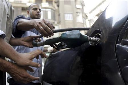People jostle for a fuel dispenser nozzle as a worker fills the tank of a car at a petrol station in Cairo October 3, 2012. REUTERS/Mohamed Abd El Ghany
