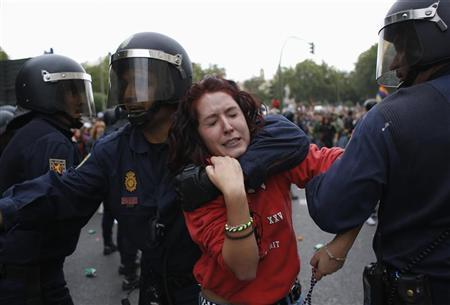 A protester is dragged away by a police officer after the police charged demonstrators outside Spanish parliament in Madrid, September 25, 2012. REUTERS/Susana Vera