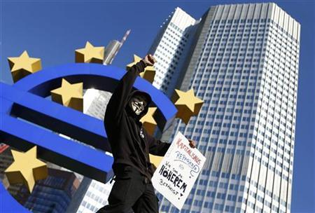 A demonstrator holds a placard as he stands at the euro sculpture in front of the headquarters of the European Central Bank (ECB) during an anti-capitalism demonstration in Frankfurt, September 29, 2012. REUTERS/Kai Pfaffenbach
