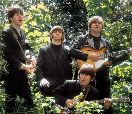 An undated handout photo shows members of the band The Beatles walk and sing as they are filmed during a promotional video for their song ''Rain'', in a garden outside Chiswick House. REUTERS/Robert Whitaker/Handout