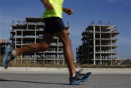 A man runs in front of a building site where construction works have been halted in Camas, near the Andalusian capital of Seville October 3, 2012. REUTERS/Marcelo del Pozo