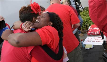 Jacqueline Robinson (R) hugs another member of the Chicago Teachers Union as they celebrate the end of their strike in Chicago September 18, 2012. REUTERS/John Gress