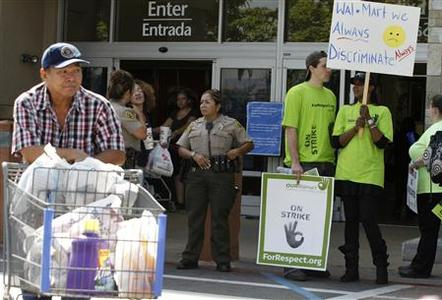 A shopper walks past Walmart workers on strike to protest over unsafe working conditions and poor wages outside a Walmart store in Pico Rivera, California, October 4, 2012. REUTERS/Jonathan Alcorn