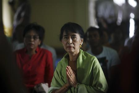 Myanmar's pro-democracy leader Aung San Suu Kyi prays with Buddhist monks at a monastery in Kawhmu township in Yangon Division August 3, 2012. REUTERS/Soe Zeya Tun