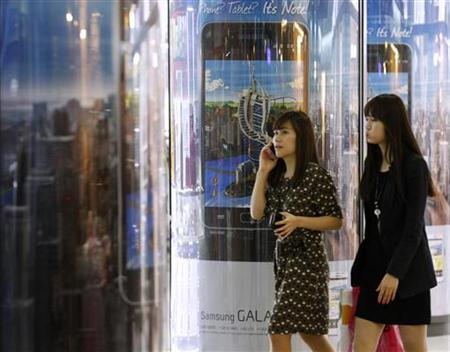 Women walk past an advertisement board promoting Galaxy Note of Samsung Electronics in Seoul April 27, 2012. REUTERS/Kim Hong-Ji