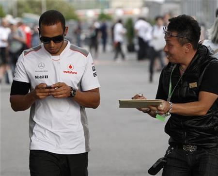 A fan asks McLaren Formula One driver Lewis Hamilton of Britain for an autograph as he walks in the paddock after the second practice session of the Japanese F1 Grand Prix at the Suzuka circuit October 5, 2012. REUTERS/Issei Kato
