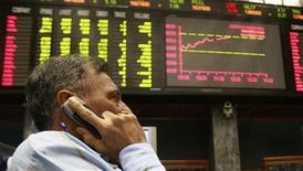 Брокер говорит по мобильному телефону в торговом зале фондовой биржи в Карачи, 24 марта 2009 года. Развивающиеся рынки вновь набирают популярность среди глобальных инвесторов, и фонды, ориентированные на Россию, оказались в первых рядах предпочтений на фоне притока свежей ликвидности в активы в результате стимулирующих мер мировых Центробанков. REUTERS/Athar Hussain