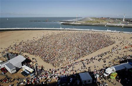 Some of around 10,000 people take part in the filming of ''The big ask again'' video clip on a beach at Oostende August 29, 2009. REUTERS/Sebastien Pirlet