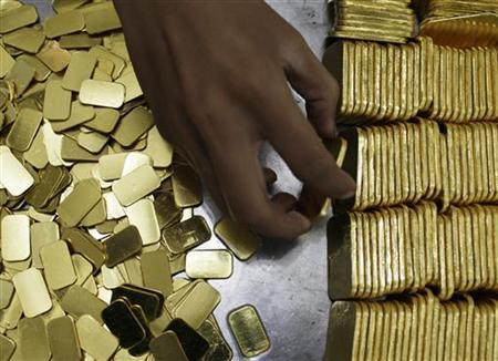 An employee holds a gold piece, each weighing 100 grams, at the state-owned mining company PT Antam Tbk metal refinery in Jakarta July 13, 2012. REUTERS/Beawiharta