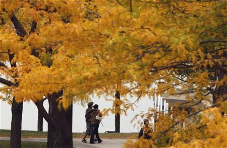 A couple walk along a path by the Maumee River in Toledo, Ohio, October 14, 2008. REUTERS/Jim Young