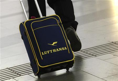 A man wheels a luggage bag with a Lufthansa logo in Vienna April 30, 2012. REUTERS/Lisi Niesner