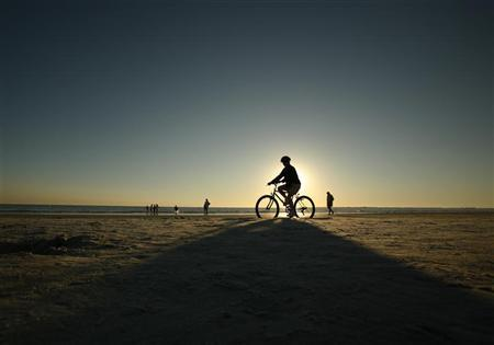A bicyclist rides on the beach in Fort Myers, Florida February 19, 2007. REUTERS/Brian Snyder (UNITED STATES)