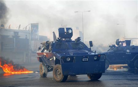 Riot police armoured personnel carriers drive on the street during clashes between police and anti-government protesters marching towards Pearl Square after visiting the grave of Mohammed Ali Moshaima in the village of Jidhafs, west of Manama, October 5, 2012. REUTERS/Stringer