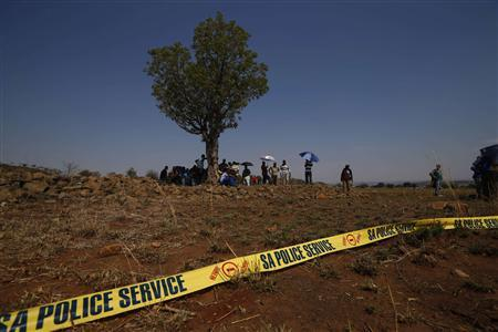 Striking platinum miners wait behind a police cordon at the site where violent clashes overnight left one person dead near the Anglo American Platinum (AMPLATS) mine in Rustenburg in South Africa's North West Province, October 5, 2012. REUTERS/Mike Hutchings