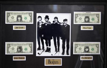 U.S $1 dollar notes with images of The Beatles and a picture of them from the movie ''Help'' are displayed at an exhibition in Buenos Aires October 4, 2011. REUTERS/Enrique Marcarian