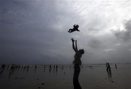 A man plays with his child against the backdrop of monsoon clouds on a beach in Mumbai July 23, 2010. REUTERS/Danish Siddiqui/Files