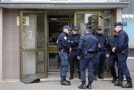 Police officers stand guard next to the entrance of a building in the Esplanade suburb of Strasbourg October 6, 2012. REUTERS/Vincent Kessler