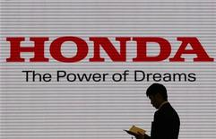 A man is silhouetted against a logo of Honda Motor at the company showroom in Tokyo January 31, 2012. REUTERS/Toru Hanai