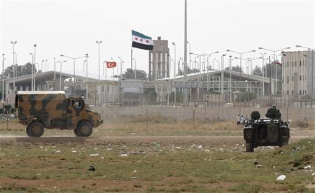Turkish troops take their position at the Akcakale border gate in southern Sanliurfa province October 7, 2012, as a Syrian Independence flag waves at Syria's Tel Abyad border crossing in the background. REUTERS/Stringer (TURKEY - Tags: POLITICS MILITARY CONFLICT)