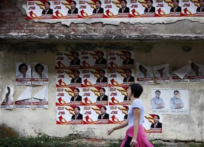 A woman walks past election posters in Srebrenica, October 6, 2012. Bosnians will vote on Sunday in local elections likely to keep in power nationalist parties reflecting ethnic rivalries, 17 years after war ended. REUTERS/Dado Ruvic IONS)