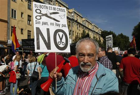 A demonstrator holds a banner during a protest against further tax hikes and austerity cuts in Madrid October 7, 2012. REUTERS/Andrea Comas