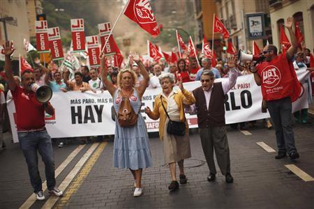 Pensioners Carmen Ruiz (C), 82, her husband Francisco Arias (2nd R), 83, and their daughter Victoria (2nd L), 54, shout the slogan, ''Hold up your hands, this is a robbery,'' during a protest against further tax hikes and austerity cuts in Malaga, southern Spain October 7, 2012. REUTERS/Jon Nazca