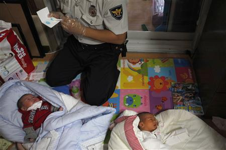 A police officer collects DNA samples from two abandoned babies after the babies were left at a ''baby box'' at Joosarang church in Seoul September 20, 2012. A South Korean pastor of the church who runs a ''baby box'' where mothers can leave unwanted infants has seen a sharp increase in the number of newborns being left there because, the pastor says, of a new law aimed protecting the rights of children. South Korea is trying to shed a reputation of being a source of babies for adoption by people abroad. It is encouraging domestic adoption and tightening up the process of a child's transfer from birth mother to adoptive parents. Picture taken September 20, 2012. REUTERS/Kim Hong-Ji