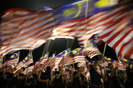 Locals from Sabah wave Malaysian flags during the Malaysia Day celebrations marking Sabah's entry into Malaysia, in Kota Kinabalu September 16, 2012. With a general election due within seven months, the 13-party ruling Barisan Nasional coalition is banking on Sabah and neighbouring Sarawak state on Borneo island to prolong its 55-year grip on power. Picture taken September 16, 2012. REUTERS/Bazuki Muhammad