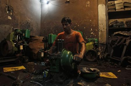 An employee works inside a power generator manufacturing workshop on the outskirts of New Delhi September 12, 2012. It is rough being an employee of Torrent Power Ltd in the Indian city of Agra. Furious residents regularly take staff of the power distributor hostage or beat them up, stone-throwing mobs besiege the firm's high-walled compound, and one official recently had to be hospitalised after he was hit on the head with a brick. Torrent's experience highlights the perils for companies hoping to benefit from the privatisation drive, as well as the challenges facing India as it grapples with chronic energy shortages that stand in the way of its ambitions to become a global economic power. Picture taken September 12, 2012. REUTERS/Mansi Thapliyal