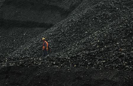 A labourer walks amid piles of coal at an opencast coal mine in Fuxin, Liaoning province in this May 30, 2012 file photo. China is spending $14 billion on pilot projects to turn coal in remote parts of the country into natural gas, a risky bet that could help meet the country's surging demand for the cleaner fuel. REUTERS/Stringer/Files