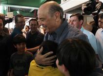Candidato do PSDB à prefeitura de São Paulo, José Serra, abraça menino após registrar seu voto. 07/10/2012 REUTERS/Paulo Whitaker