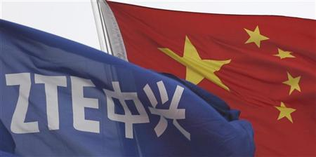 A ZTE flag flutters in front of the Chinese national flag outside its headquarters in Shenzhen, Guangdong province April 17, 2012. REUTERS/Tyrone Siu