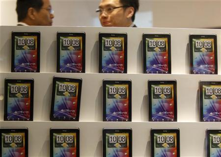 People walk past a wall displaying mockup HTC mobile phones at a shopping mall in Taipei November 24, 2011. REUTERS/Pichi Chuang