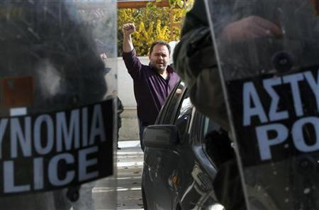 Nikos Fotopoulos, head of Greece's public power corporation workers union (GENOP), raises his hand after he was arrested by police in Athens November 24, 2011. REUTERS/John Kolesidis