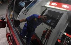 Мужчина заправляет автомобиль на заправке в Хэфэй, 11 сентября 2012 года. Китай планирует потратить $14 миллиардов на пилотные проекты получения газа из угля в рамках программы по переходу на более экологически чистое топливо. REUTERS/Stringer (CHINA - Tags: BUSINESS ENERGY)