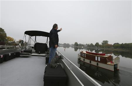 Semi-retired Ian Morton waves to another houseboat as it navigates through the waterway in Le Port De Plaisance de Lachine, a marina in Montreal, Quebec, October 4, 2012. REUTERS/Christinne Muschi