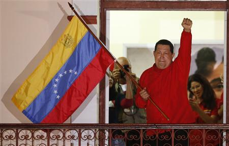 Venezuelan President Hugo Chavez waves the national flag while celebrating from a balcony at Miraflores Palace in Caracas October 7, 2012. REUTERS/Jorge Silva