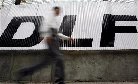 A man walks past a logo of Indian property developer DLF Ltd. in Mumbai June 11, 2007. REUTERS/Punit Paranjpe/Files