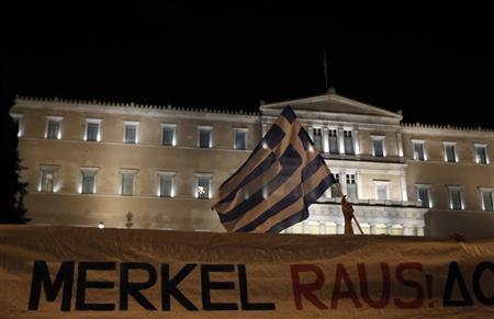 Protesters hold a banner in front of the parliament during a rally against the upcoming visit by German Chancellor Angela Merkel in Athens October 8, 2012. REUTERS/John Kolesidis