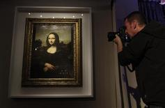 "A photographer take a picture of a portrait of Mona Lisa on a painting attributed to Leonardo da Vinci during a presentation in Geneva September 27, 2012. A package of diaries said to have been posted to the United States from Britain in the 1960s could provide a vital clue to the origin of a controversial portrait presented in Geneva last month as Leonardo da Vinci's original ""Mona Lisa."" Picture taken September 27, 2012. REUTERS/Denis Balibouse"