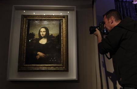 A photographer take a picture of a portrait of Mona Lisa on a painting attributed to Leonardo da Vinci during a presentation in Geneva September 27, 2012. A package of diaries said to have been posted to the United States from Britain in the 1960s could provide a vital clue to the origin of a controversial portrait presented in Geneva last month as Leonardo da Vinci's original ''Mona Lisa.'' Picture taken September 27, 2012. REUTERS/Denis Balibouse