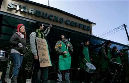 Starbucks employees protest in front of the company's cafe in Santiago in this file photo taken July 25, 2011. REUTERS/Victor Ruiz Caballero