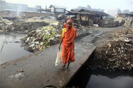 A woman crosses a bridge next to a tannery factory by the river Buriganga at Hazaribagh in Dhaka July 12, 2012. REUTERS/Andrew Biraj