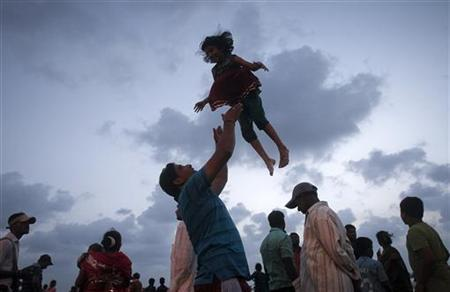 Rithika, six years old, is tossed into the air by her father as they join devotees at the Arabian Sea on the fifth day of the ten-day-long Ganesh Chaturthi festival in Mumbai, September 23, 2012. REUTERS/Vivek Prakash/Files