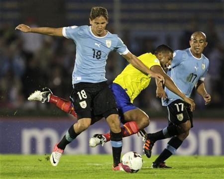 Uruguay's Gaston Ramirez (L) fights for the ball witth Ecuador's Antonio Valencia (C) as Uruguay's Egidio Arevalo looks on during their 2014 World Cup qualifying match in Montevideo September 11, 2012. REUTERS/Andres Stapff