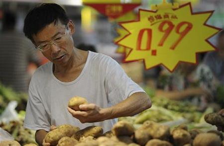 A customer selects potatoes at a supermarket in Hefei, Anhui province, August 9, 2012. REUTERS/Stringer