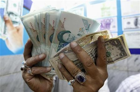 A vendor inspects Iranian rials at a currency exchange shop in Baghdad, October 4, 2012. REUTERS/Thaier al-Sudani
