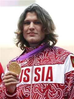 Russian's Ivan Ukhov holds up his gold medal for men's high jump in London at the London 2012 Olympic Games at the Olympic Stadium August 8, 2012. REUTERS/Eddie Keogh