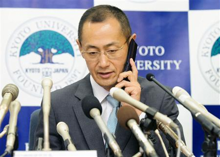 Kyoto University Professor Shinya Yamanaka talks with Japan's Prime Minister Yoshihiko Nada by a mobile phone during a news conference in Kyoto, western Japan, in this photo taken by Kyodo October 8, 2012. REUTERS/Kyodo